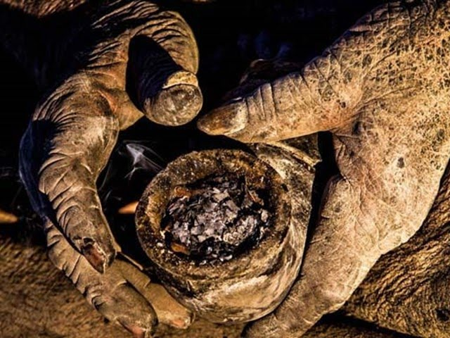 Hadji piposuyla hayvan gübresini ciğerlerine çekiyor.